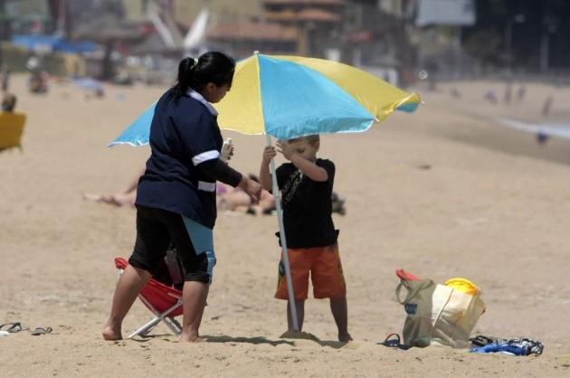 Nana cuida a niño  mientras madre toma sol | Francisco
