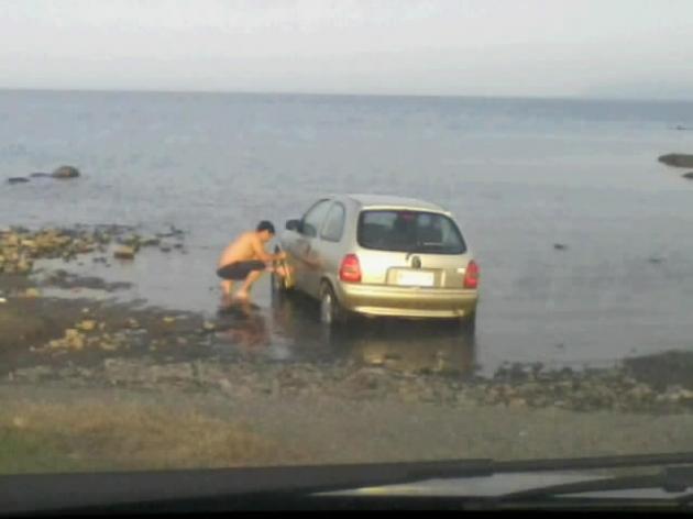 Hombre lavando su auto en el lago Llanquihue | Roxana Almonacid
