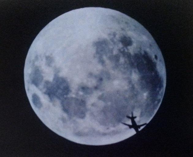Imagen de un avión luciéndose sobre la Luna llena | Arturo Gómez