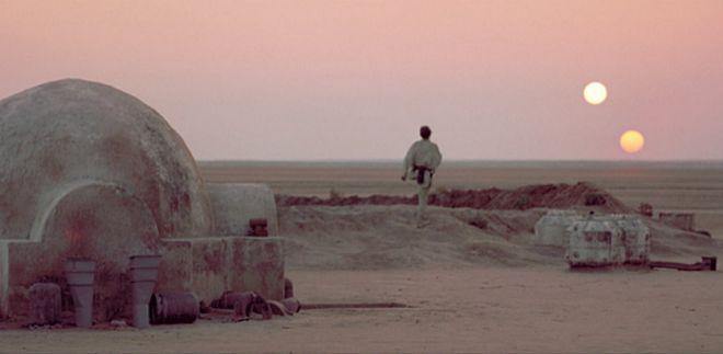 Luke Skywalker en Tatooine y al fondo, los dos soles que orbita el planeta, en un fotograma de 'Star Wars'.