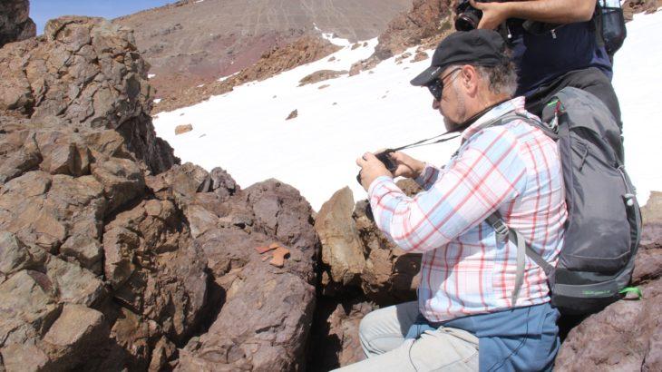 """El Dr. Rubén Stehberg fotografiando la roca ceremonial o """"huaca"""" del sitio."""