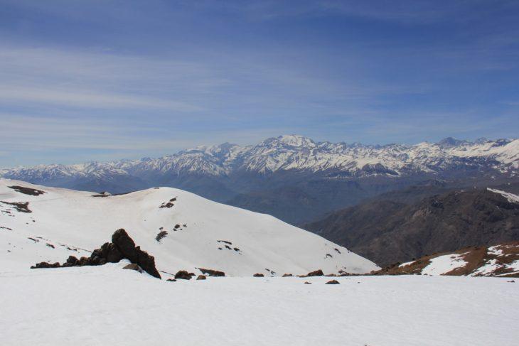 """Vista de la roca ceremonial o """"huaca"""" con el cerro El Plomo al fondo."""
