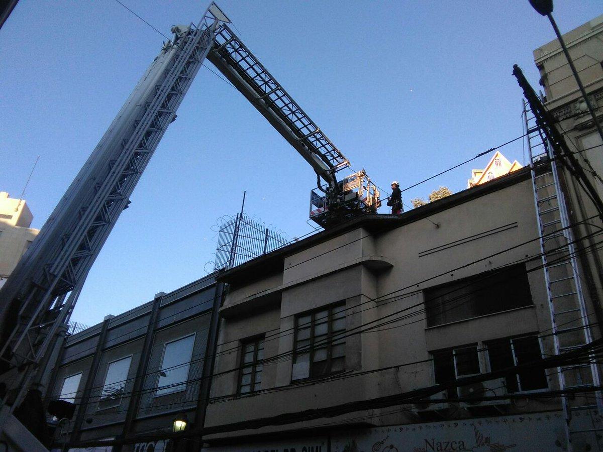 Bomberos rescata a mujer desde techumbre de edificio