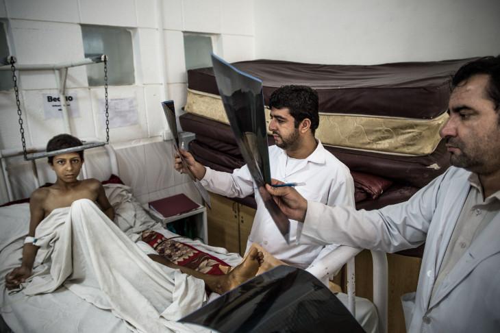 Nissan, de 14 años, está siendo examinado en la guardia de ortopedia. A la derecha se encuentra el Dr. Mohammadin Narriwal, uno de los cirujanos ©Kadir van Lohuizen/Noor
