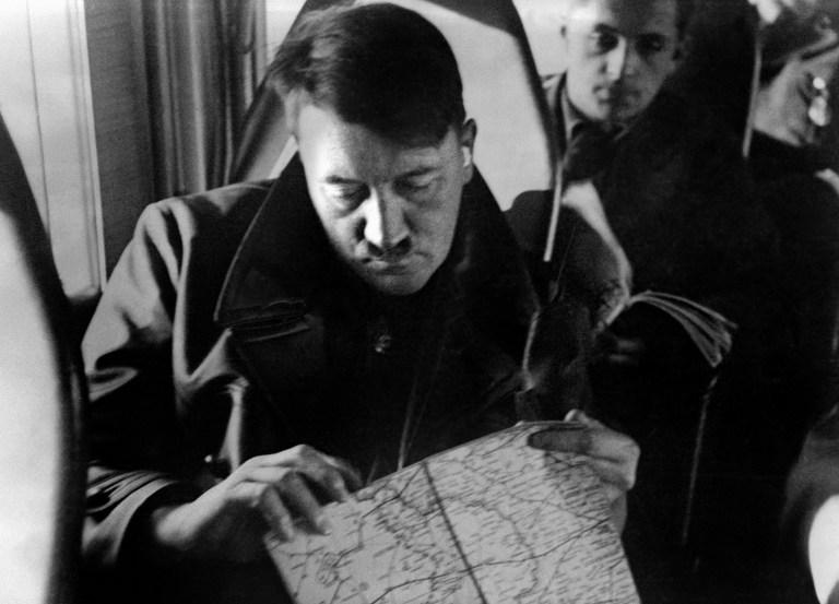 Adolf Hitler observando mapas a bordo de un avión.