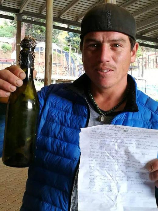 Pescador junto a la botella y el mensaje encontrado