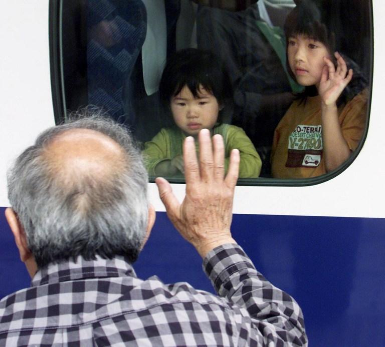 Un abuelo japonés despide a sus nietos en la estación de tren | AFP