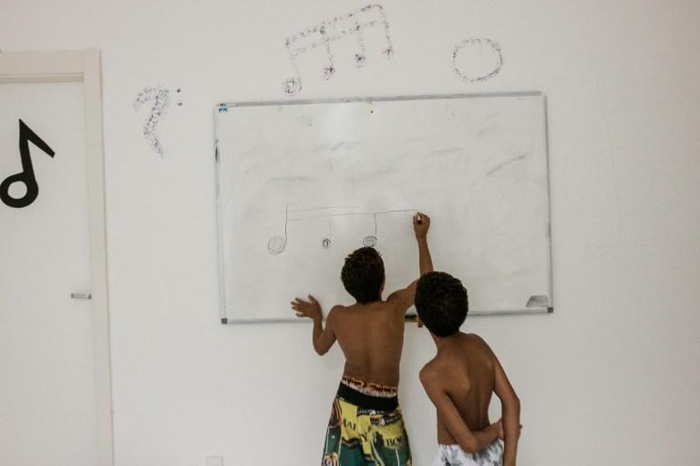 Dos niños toman una clase de música gratuita dentro de una estación del inactivo sistema de teleférico | Agencia AFP | Yasuyoshi Chiba
