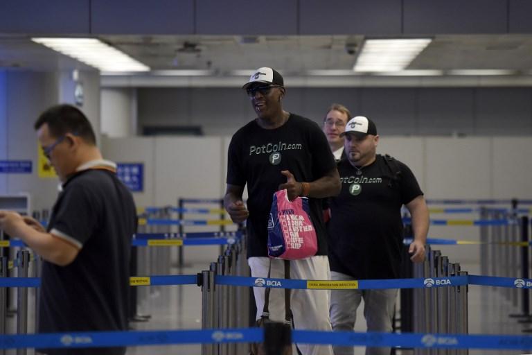 Dennis Rodman (al centro) cargando su bolsa de regalos en su visita a Corea del Norte | Wang Zhao | AFP
