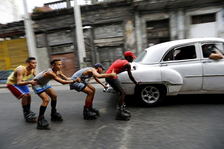 Adolescentes en patines se afirman unos a otros mientras son jalados por un vehículo de época para moverse a lo largo de una calle, en Habana, Cuba Marzo 19, 2016.