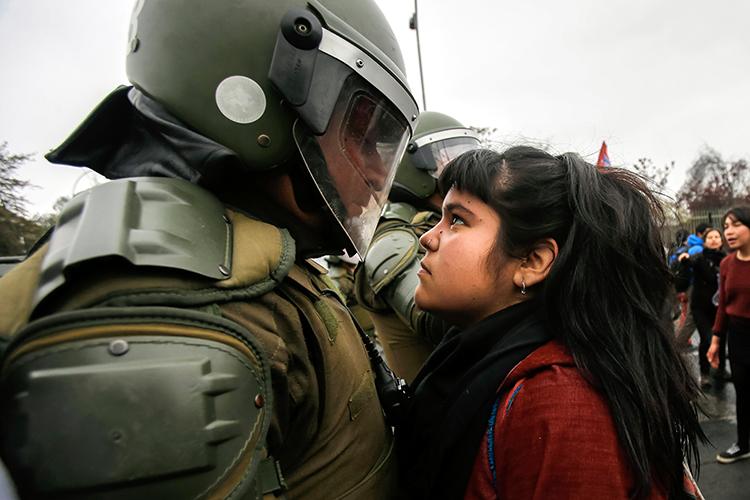 Una manifestante enfrenta mirada a policía antidisturbio durante una movilización/protesta que marca el golpe militar del país en 1973, en Santiago de Chile el 11 de septiembre de 2016.