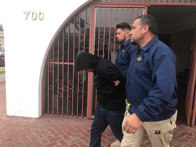 Detenido siendo llevado por la PDI