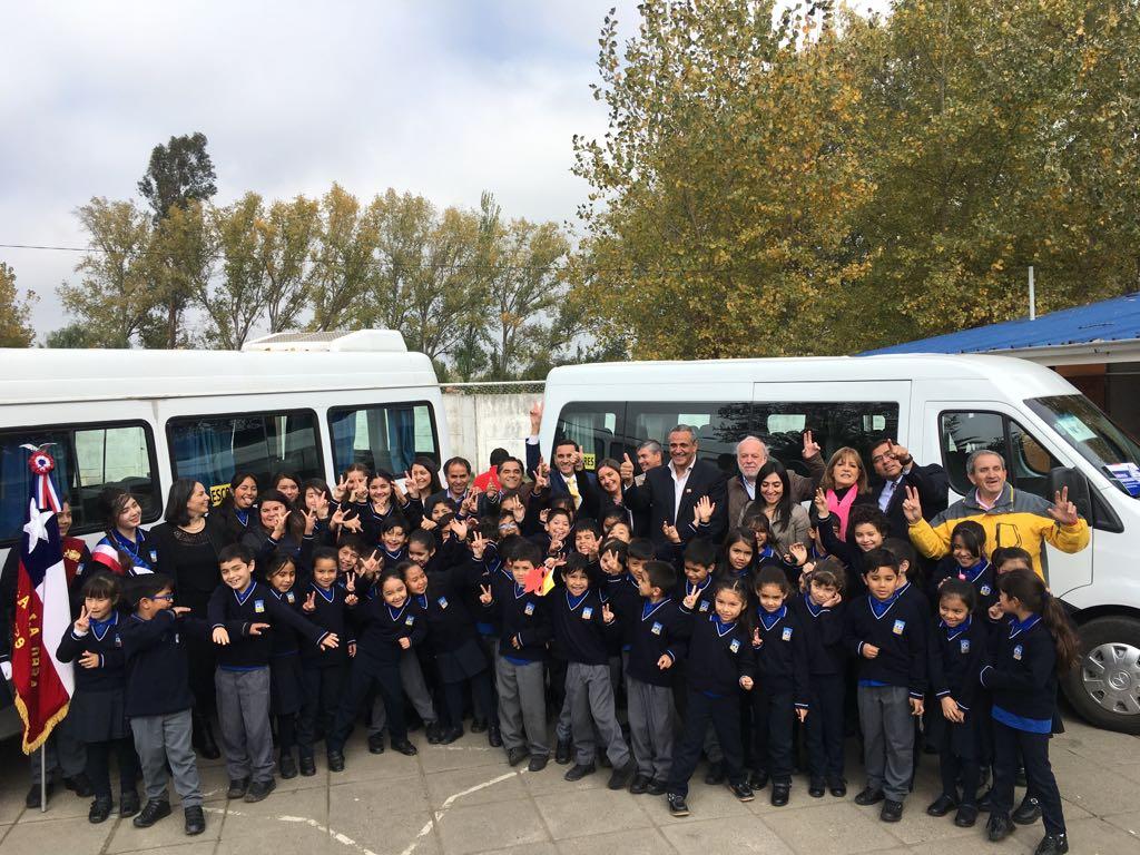 Niños, autoridades y vehículos escolares en ceremonia.