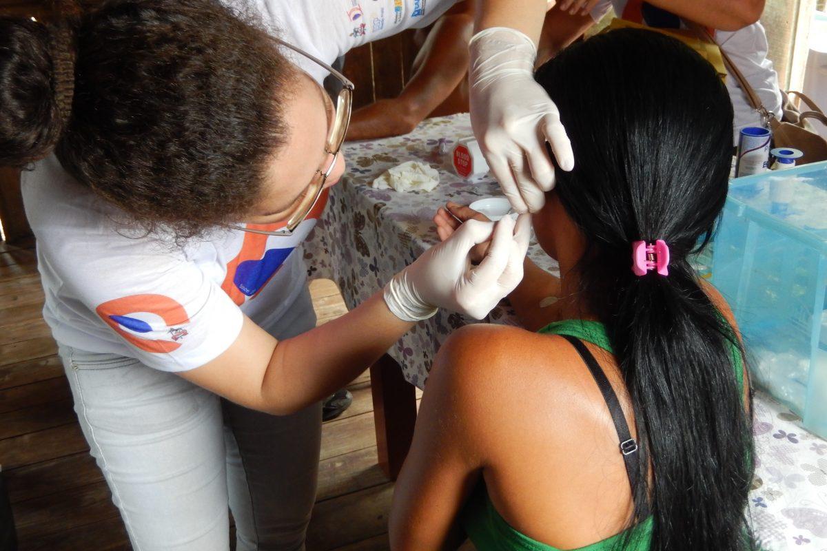 Un técnico de campo extrae sangre y obtiene una muestra de la piel del lóbulo de la oreja para la prueba. Imagen de John Spencer