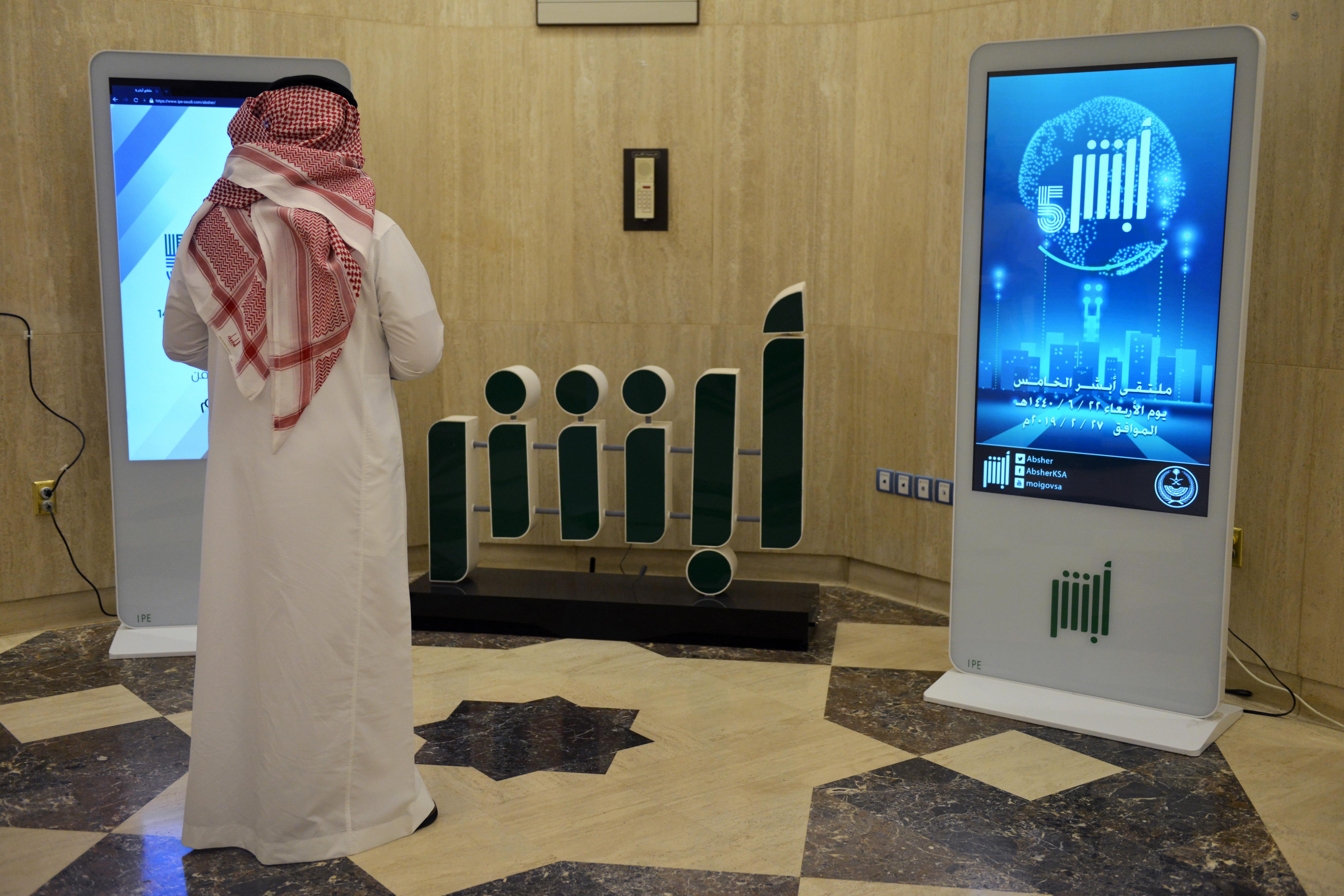 Un empleado del Ministerio del Interior de Arabia Saudita frente a una pantalla que muestra la aplicación Absher | Fayez Nureldine | Agence France-Presse