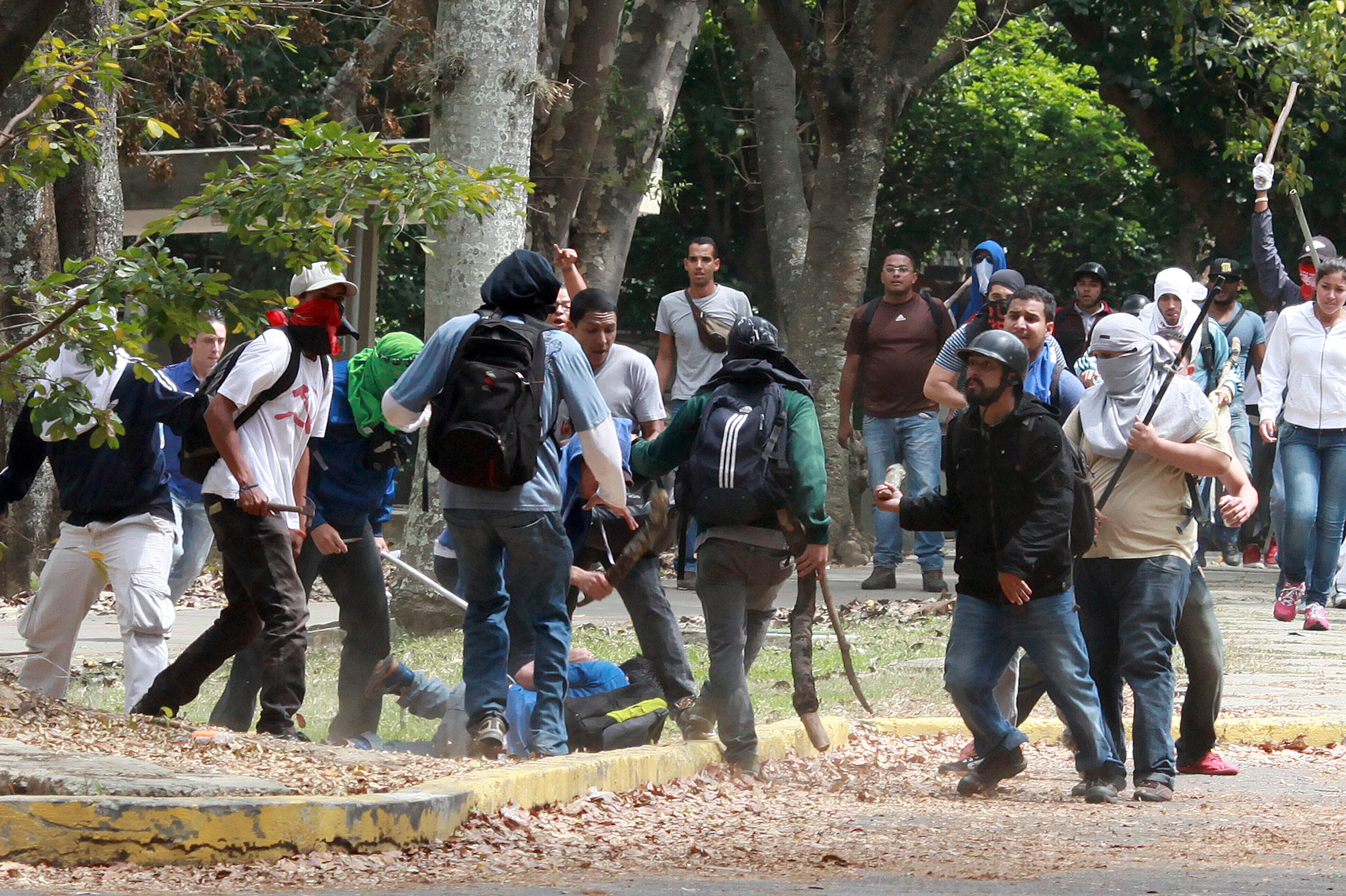 Miembros de un colectivo pro Maduro golpeando a un estudiante que protestaba contra el gobierno en 2014 | Federico Parra | Agence France-Presse