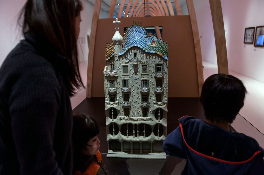 """A woman and children look at a scale model of Casa Batllo by Spanish renowned architect Antonio Gaudi, during the exhibition """"Gaudi in Valparaiso"""" at Parque Cultural Valparaiso, in Valparaiso, Chile, on April 09, 2019. - The exhibition running from March 12 to May 10, 2019 displays 152 Gaudi original pieces, 13 audiovisuals, and several multimedia installations. (Photo by Martin BERNETTI / AFP) / RESTRICTED TO EDITORIAL USE - MANDATORY MENTION OF THE ARTIST UPON PUBLICATION - TO ILLUSTRATE THE EVENT AS SPECIFIED IN THE CAPTION"""