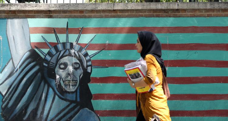 Mujer pasa frente a mural de exembajada de EEUU en Teherán | Agence France-Presse