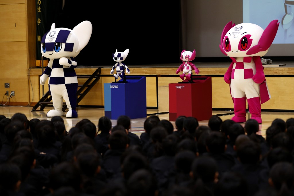 """Tokyo 2020 Olympic and Paralympic Games' mascots and robot-type mascots Miraitowa (L) and Someity (R) attend a ceremony at Hoyonomori elementary school in Tokyo on November 18, 2019. - Tokyo 2020 Summer Games' mascot robots visited an elementary school, drawing cheers and laughters from children as they gave them quizzes and responded to verbal instructions. (Photo by Behrouz MEHRI / AFP) / """"The erroneous mention[s] appearing in the metadata of this photo by Behrouz MEHRI has been modified in AFP systems in the following manner: [Miraitowa] instead of [Miraito]. Please immediately remove the erroneous mention[s] from all your online services and delete it (them) from your servers. If you have been authorized by AFP to distribute it (them) to third parties, please ensure that the same actions are carried out by them. Failure to promptly comply with these instructions will entail liability on your part for any continued or post notification usage. Therefore we thank you very much for all your attention and prompt action. We are sorry for the inconvenience this notification may cause and remain at your disposal for any further information you may require."""""""