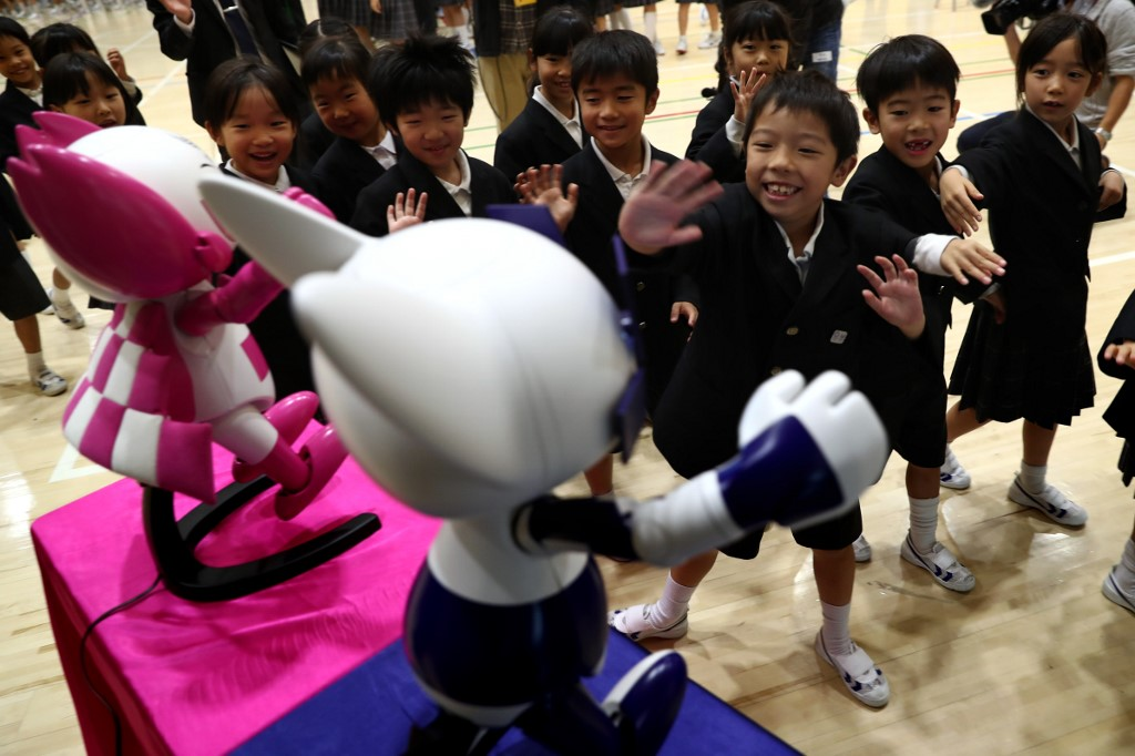 """Schoolchildren interact with Tokyo 2020 Olympic and Paralympic Games' robot-type mascots Miraitowa and Someity during a ceremony at Hoyonomori elementary school in Tokyo on November 18, 2019. - Tokyo 2020 Summer Games' mascot robots visited an elementary school, drawing cheers and laughters from children as they gave them quizzes and responded to verbal instructions. (Photo by Behrouz MEHRI / AFP) / """"The erroneous mention[s] appearing in the metadata of this photo by Behrouz MEHRI has been modified in AFP systems in the following manner: [Miraitowa] instead of [Miraito]. Please immediately remove the erroneous mention[s] from all your online services and delete it (them) from your servers. If you have been authorized by AFP to distribute it (them) to third parties, please ensure that the same actions are carried out by them. Failure to promptly comply with these instructions will entail liability on your part for any continued or post notification usage. Therefore we thank you very much for all your attention and prompt action. We are sorry for the inconvenience this notification may cause and remain at your disposal for any further information you may require."""""""
