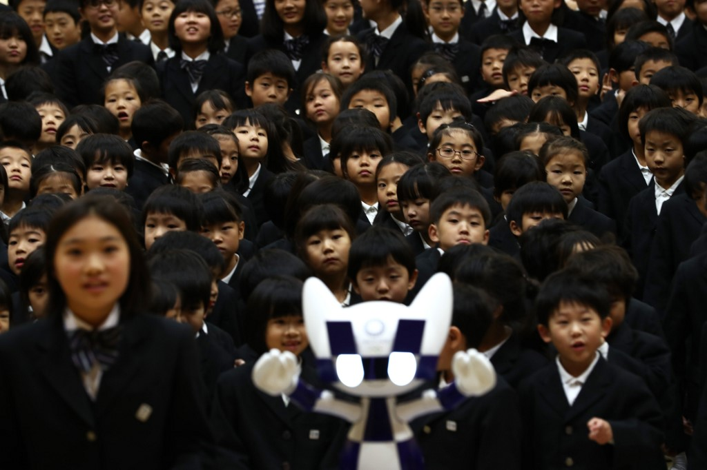 """Schoolchildren pose for a picture with Tokyo 2020 Olympic Games' robot-type mascot Miraitowa during a ceremony at Hoyonomori elementary school in Tokyo on November 18, 2019. - Tokyo 2020 Summer Games' mascot robots visited an elementary school, drawing cheers and laughters from children as they gave them quizzes and responded to verbal instructions. (Photo by Behrouz MEHRI / AFP) / """"The erroneous mention[s] appearing in the metadata of this photo by Behrouz MEHRI has been modified in AFP systems in the following manner: [Miraitowa] instead of [Miraito]. Please immediately remove the erroneous mention[s] from all your online services and delete it (them) from your servers. If you have been authorized by AFP to distribute it (them) to third parties, please ensure that the same actions are carried out by them. Failure to promptly comply with these instructions will entail liability on your part for any continued or post notification usage. Therefore we thank you very much for all your attention and prompt action. We are sorry for the inconvenience this notification may cause and remain at your disposal for any further information you may require."""""""