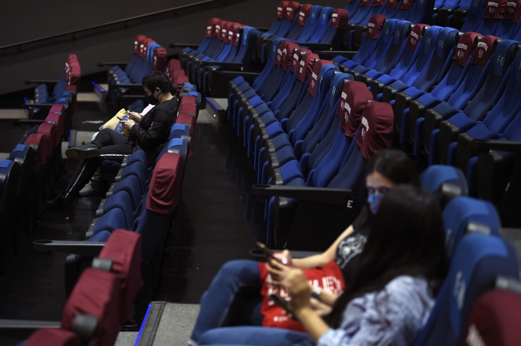 People wearing facemasks wait in a cinema hall of the Cineteca Nacional in Mexico City, on August 12, 2020 as museums, cinemas and pools are reopening in Mexico as part of the easing of restrictions amid the COVID-19 novel coronavirus pandemic. - The novel coronavirus has killed at least 743,199 people, 53,929 in Mexico, since the outbreak emerged in China last December, according to a tally from official sources compiled by AFP at 1100 GMT on Wednesday. (Photo by ALFREDO ESTRELLA / AFP)