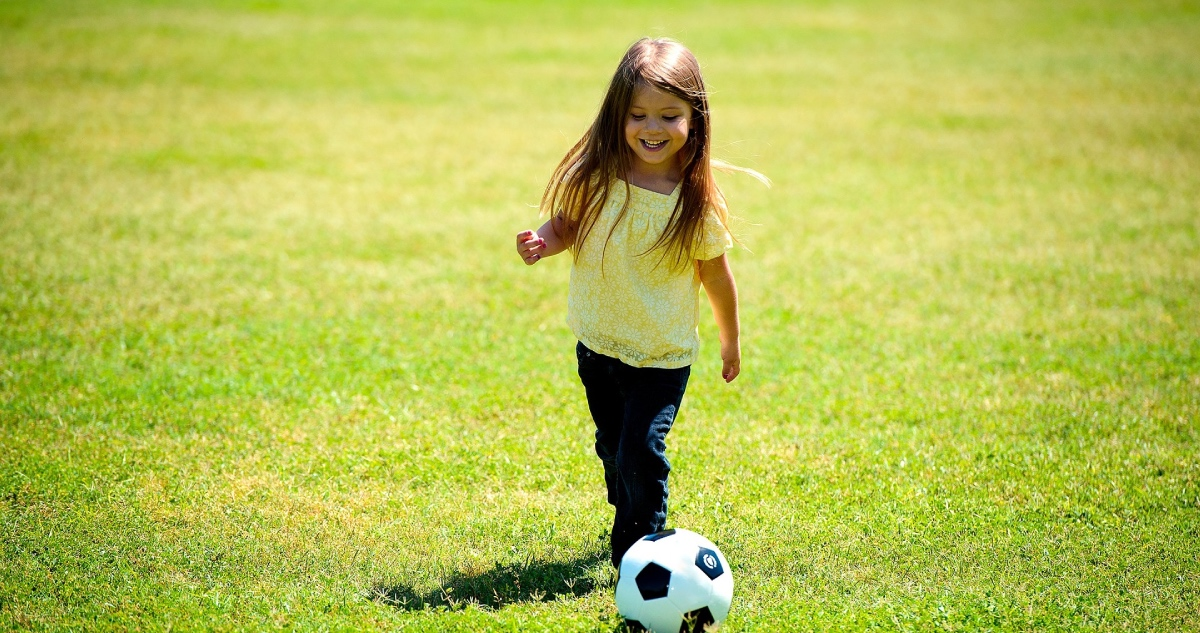 niña jugando a la pelota en el Día del Niño